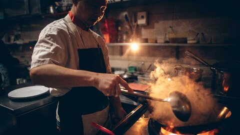 Chef stands in a dark kitchen in front of a steaming pan