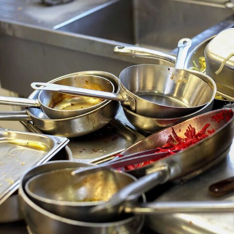 Dirty pots and pans are piled up in the kitchen's sink